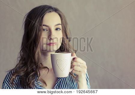 Beautiful teenage girl in striped shirt drinking coffee or tea from white cup in the morning. Portrait of sad young woman with curly fair hair wearing pajamas enjoying her beverage. Copy space.