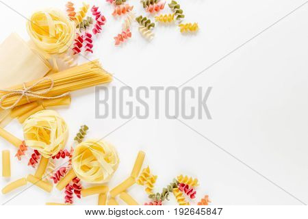 Assortment of different shape italian pastas on white background top view copyspace.