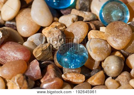 Blue glass pebbles among tumbled rocks of various origins in the sunshine.