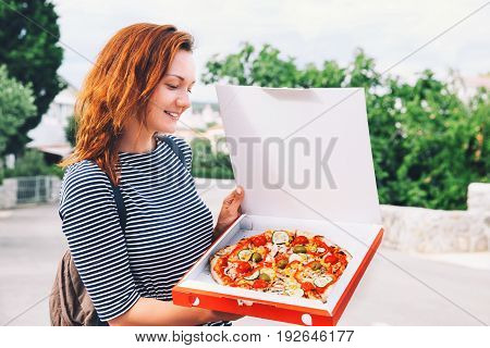 Happy Young Woman Holding Hot Pizza In Box
