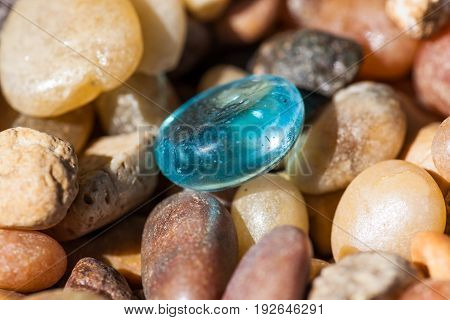 One blue glass pebble lays among small tumbled rocks of various origin in the sunshine.