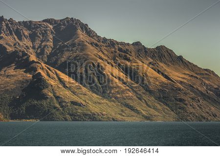 Queenstown New Zealand - March 16 2017: Dark brown Mountain slopes on Lake Wakatipu show orange golden broom. Blue sky and water.