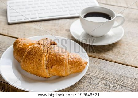 Businessman morning with keyboard, cup of coffee and croissant for lunch on wooden table background
