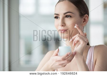 Portrait of jolly young girl holding jar with cream in hands and applying it on skin by finger. She is looking to distance with smile. Copy space in left side