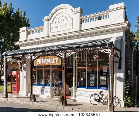 Arrowtown New Zealand - March 16 2017: The white painted old building of the active pharmacy in town. Bike and red phone booth in shot. Posters in window.
