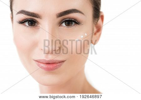 Portrait of jolly beautiful girl with three dots of cream on her cheek. She is having natural make-up and smiling