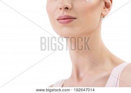 Close up of neck and lower part of face of young beautiful woman. She is having dots of cream on her cheek and lipstick on lips. Isolated and copy space in left side