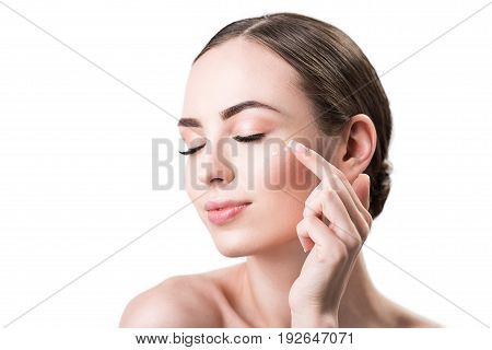 Close up of face and hand of happy young woman applying cream on cheek by point finger. She is closing her eyes with pleasure. Isolated and copy space in left side