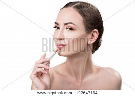 Portrait of happy young woman putting rosy lipstick on her lips. She is holding gloss stick in one hand and looking to distance with smile. Isolated and copy space in left side