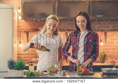 Young female friends cooking meal together at home using dress salad