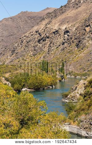 Cromwell New Zealand - March 15 2017: Kawarau River meanders and cuts a narrow gorge through dry brown mountains. Green vegetation borders river. Blue sky.