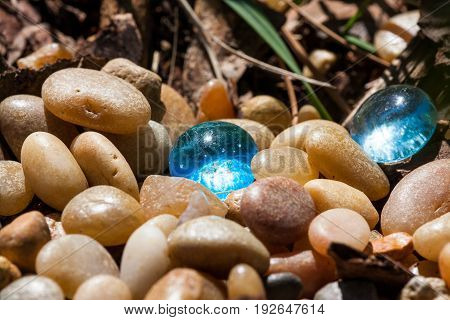Sunshine lights up two blue glass pebbles scattered among small tumbled rocks in garden landscaping.
