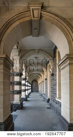 Dunedin New Zealand - March 15 2017: Long corridor with bows and pillars beige and gray stones of historic railway station against. view through the arches.