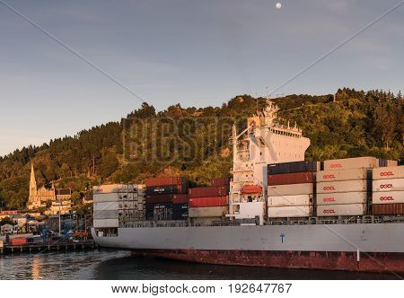 Port Chalmers New Zealand - March 15 2017: The loaded OOCL Dalian container ship is docked. Early morning light with church and houses in back. Arched by green forested hill under blue sky with moon.