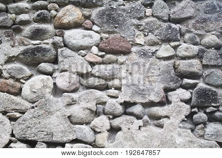 Old medieval stone wall. Medieval fortification photo texture. Rustic stone wall with cement plaster. Durable paving of old building. Grey stone texture for wallpaper or background. Rustic surface
