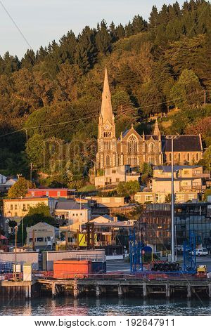 Port Chalmers New Zealand - March 15 2017: Iona Church under sunrise light towers over the harbor. Green forested hill in back. Houses traffic and working harbor in front.