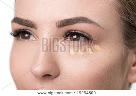 Close up of eyes of young beautiful woman with dots of foundation under one eye. Isolated