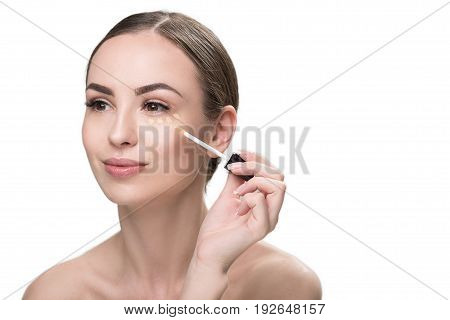 Portrait of cheerful young woman spreading foundation on her face. She is putting dots of base under her eye by special applicator. Isolated and copy space in right side