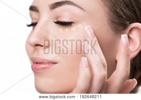 Close up of face and fingers of jolly young woman putting foundation dots under her eye. She is doing it with great pleasure, half closing her eyes. Isolated