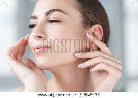 Close up of face and hands of happy young lady enjoying her fresh make-up and look. She is slightly touching her chin and cheek by her fingers with French manicure and smiling with pleasure