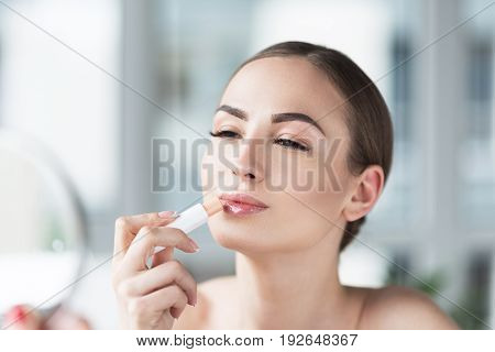 Portrait of happy young woman holding lipstick in hand and applying it on lips. She is raising slightly her head and half closing her eyes with pleasure. Copy space in left side