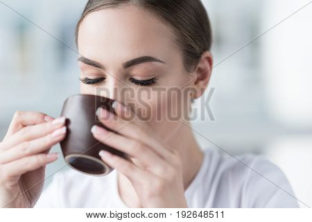 Close up of hands and face of young attractive lady holding cup by both hands and drinking coffee. Focus on her closed eyes and long eyelashes