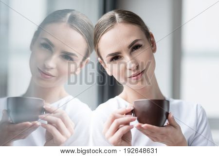 Portrait of cheery young lady with beautiful make-up holding coffee cup on her palm. She is leaning by her head on glass wall, reflecting in it