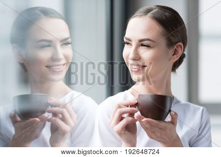 Cheerful young woman is standing with cup of coffee in hands nearby glass wall and looking at her reflection in it. She is wearing light make-up and smiling broadly