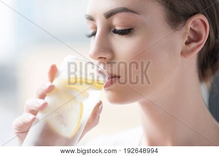 Close up of head and hand of serious young attractive woman holding glass of fresh lemonade and drinking it. She is wearing light make-up and keeping her eyes closed with delight