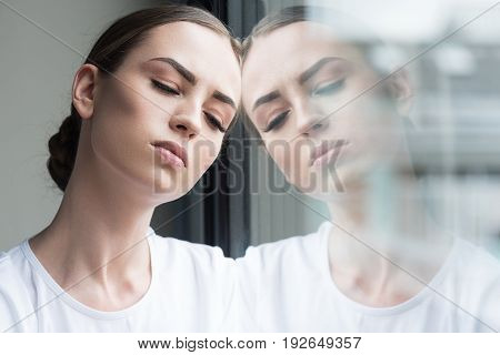 Portrait of sad young woman bowing her head to window. She is closing her eyes from sorrow and reflecting in window glass