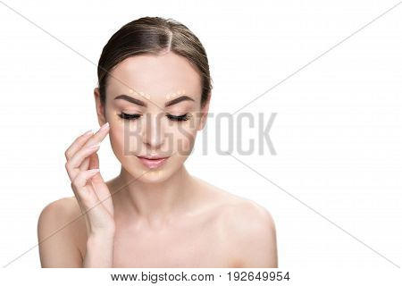 Lovely young lady is applying beige foundation on her face and looking down with light smile. Portrait. isolated