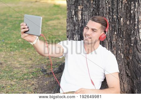 Young Latin Man Taking Selfie With Tablet.