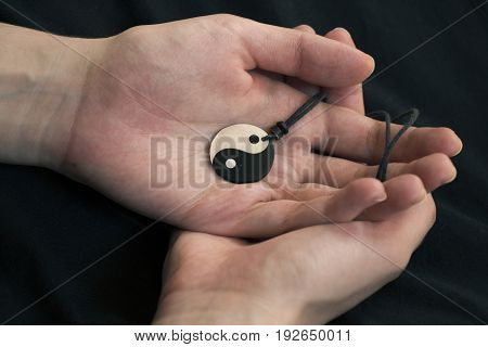 Two hands holding pearl yin yang necklace on dark background.