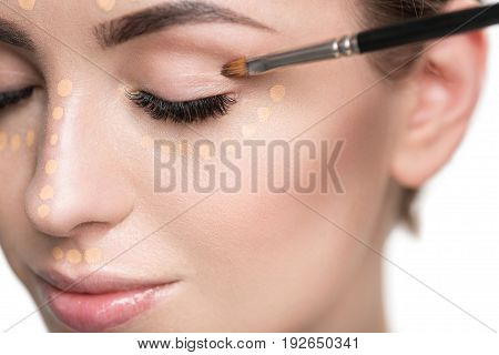 Lovely young lady is using small tassel for creating base make-up. close up of her eye. Isolated