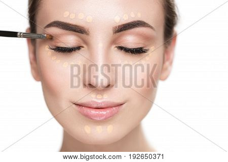 Cheerful young lady is using special brush for applying eye shadows. Portrait. Isolated