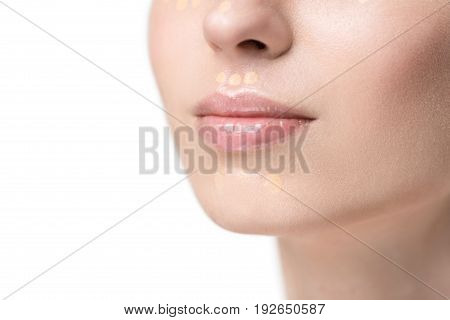 Attractive woman has beige concealer drops on her chin. Close up of female gloss lips