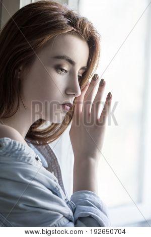 sensual sad female portrait with near window