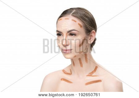 Pretty girl is using different foundations on her face, neck and clavicles. Portrait. Isolated and copy space