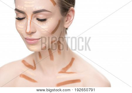 Attractive woman has various concealers on her visage and clavicles. Portrait. Isolated and copy space