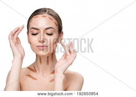 Attractive young lady is applying various concealers on face and clavicles. Isolated. Copy space on right side