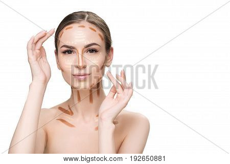 Thoughtful girl is applying various lines, drops of concealer on face and looking at camera with light smile. Portrait. Isolated and copy space