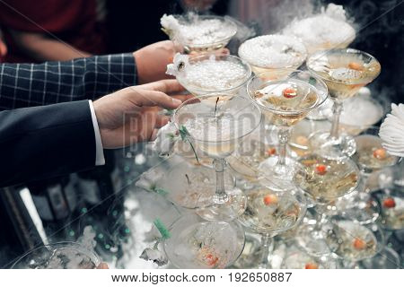 people take the glasses of champagne pyramid. close-up. pyramid of glasses for champagne at outdoor garden in wedding ceremony