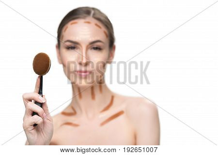 Confident lady with various concealers on her face is showing special cosmetic tassel and looking at camera with assurance. Focus on tool of cosmetology. Portrait. Isolated and copy space