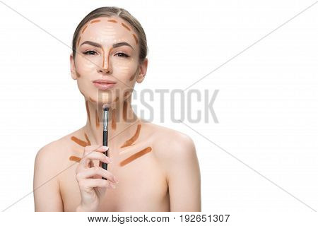 Smiling attractive woman is holding cosmetic tassel near chin and looking at camera with confidence. She using various tones of concealer. Portrait. Isolated and copy space