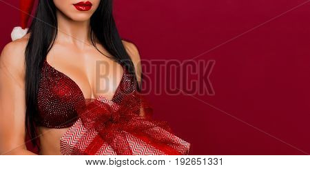 Crop close up female perfect breast in red bra holding present on red plain background.