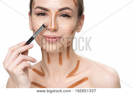 Cheerful lady is going to use cosmetic brush on her face, painted with correctors and looking at camera with smile. Portrait. Isolated