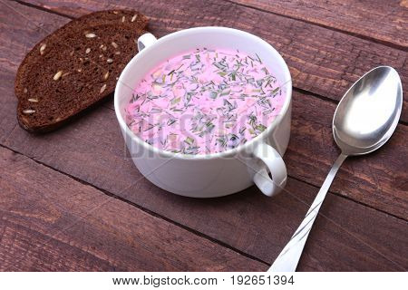 Popular spring cold soup okroshka with yoghurt. Okroshka in a bowl and slices bread on wooden table. Selective focus.