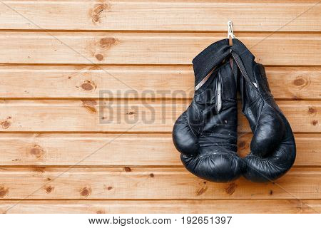 Old black pair of boxing gloves hanging in a rustic wooden wall.