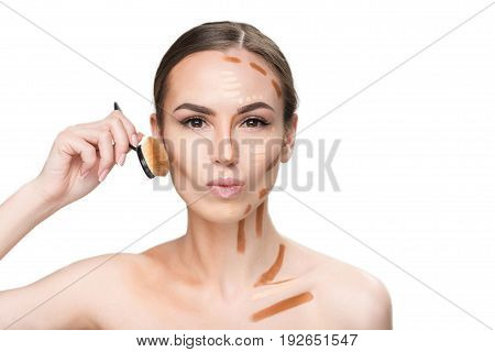 Assured pretty lady is shading correctors on her cheek and looking at camera with interest. Portrait. Isolated and copy space
