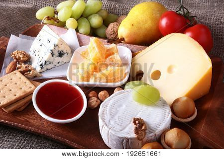 Assortment of cheese with fruits, grapes and nuts on a wooden serving tray